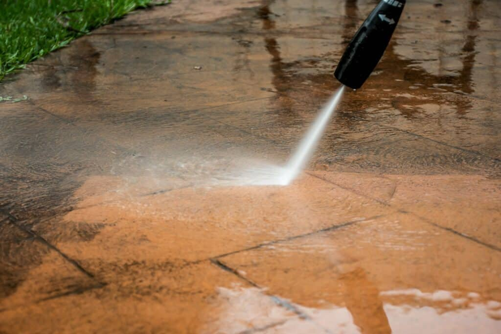 Cleaning backyard with pressure washer. Spring clean up